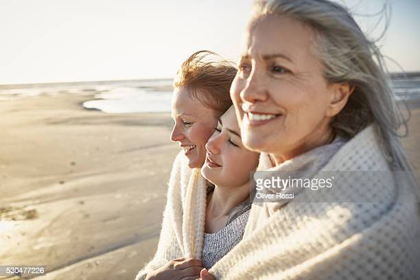 Grandmother, mother and daughter wrapped in a blanket on the beach