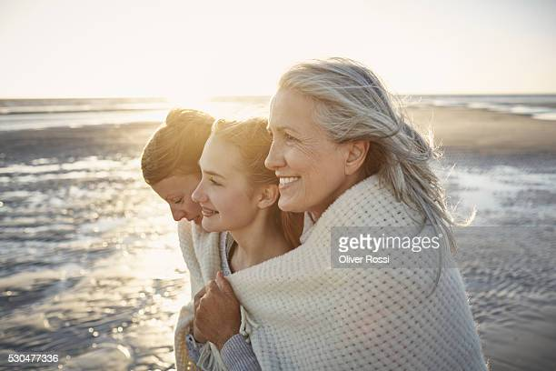 grandmother, mother and daughter wrapped in a blanket on the beach - drei personen stock-fotos und bilder