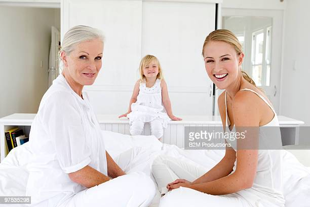 grandmother, mother and girl (3-4) on bed - beautiful granny stock photos and pictures