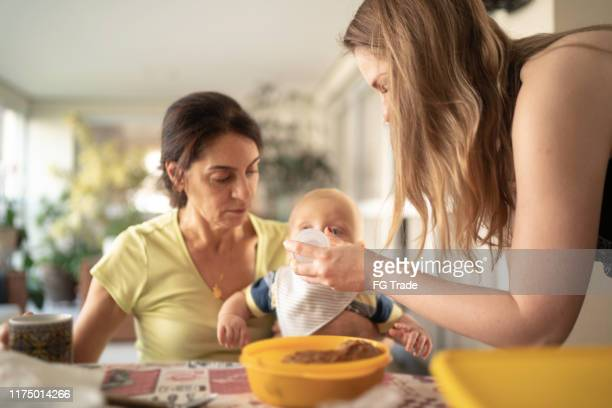 grandmother, mother and grandson having breakfast together - mother in law stock pictures, royalty-free photos & images
