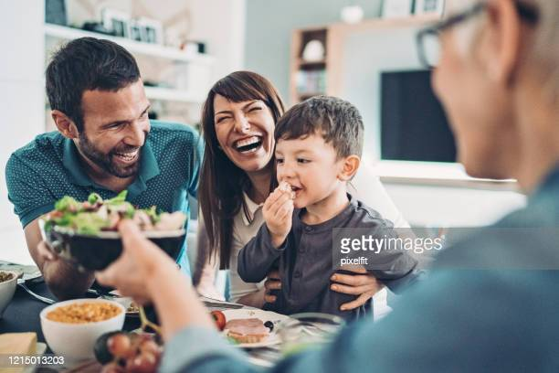 grandmother, mother, father and a boy having lunch - comida e bebida imagens e fotografias de stock