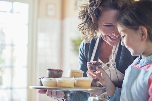 Grandmother offering granddaughter cupcakes - gettyimageskorea