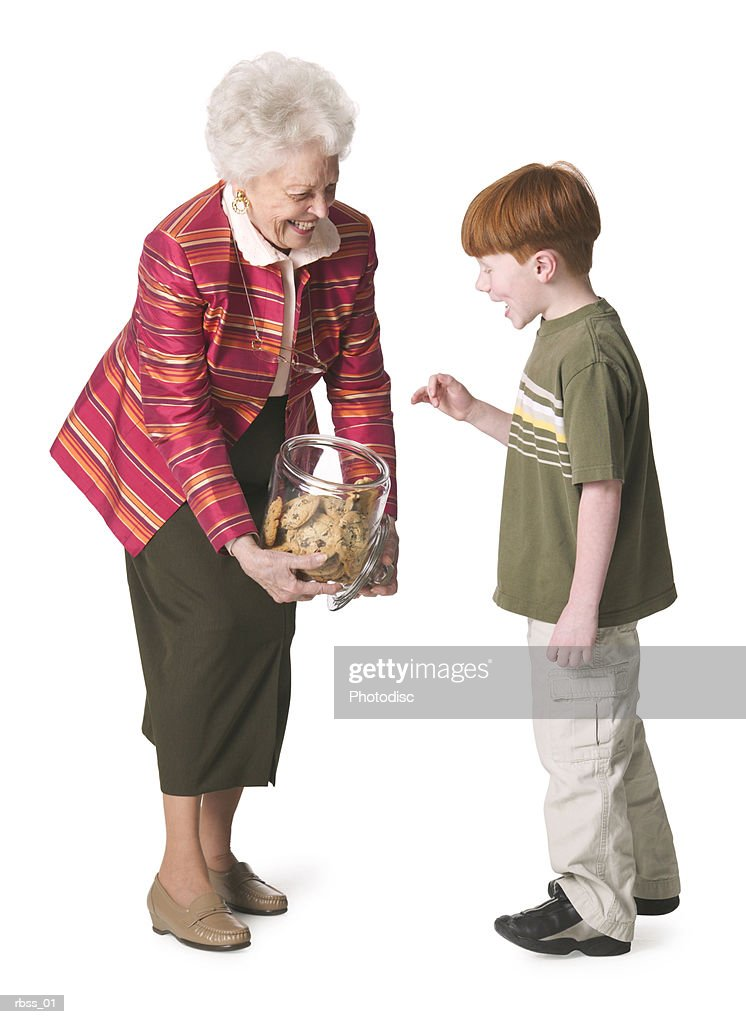 Grandmother offers a cookie to her grandson. : Stockfoto