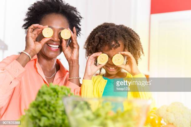 grandmother or mother and daughter cooking together in home kitchen. - funny black girl stock photos and pictures