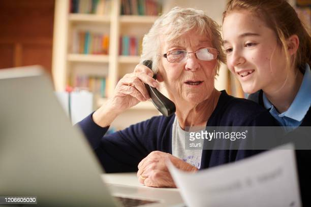 grandmother paying by telephone - grandma invoice stock pictures, royalty-free photos & images