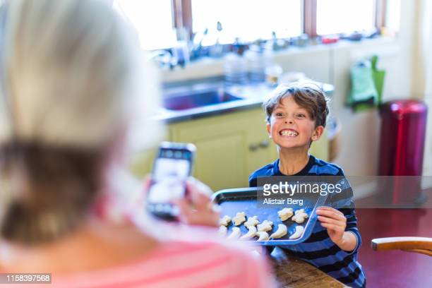 Grandmother photographing her grandson in kitchen with phone