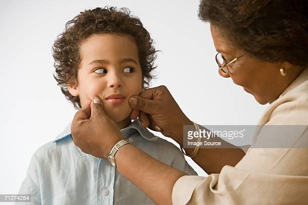 Grandmother pinching grandson's cheeks
