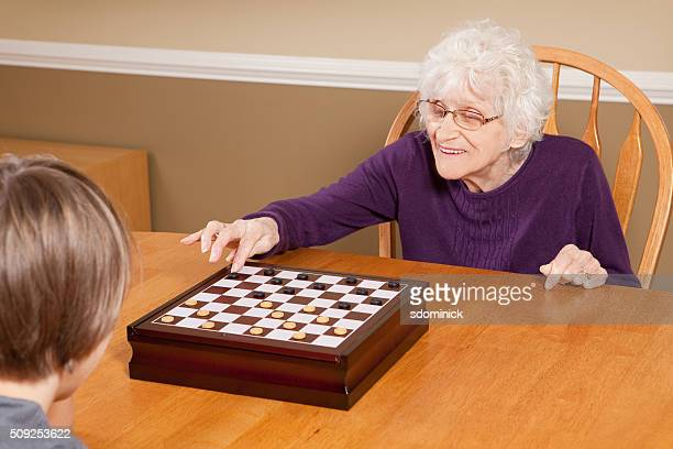 Grandmother Playing Checkers With Grandson