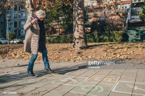 grandmother playing hopscotch - hopscotch stock pictures, royalty-free photos & images