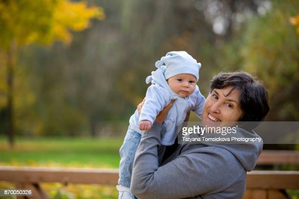 Grandmother playing in the park with her newborn baby grandchild during autumn