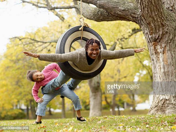 Grandmother playing with granddaughter on tyre swing