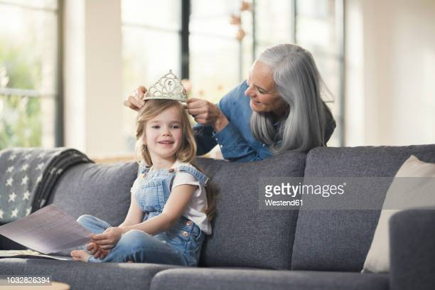 grandmother playing with granddaughter, puuting crown on her head - princess stock pictures, royalty-free photos & images