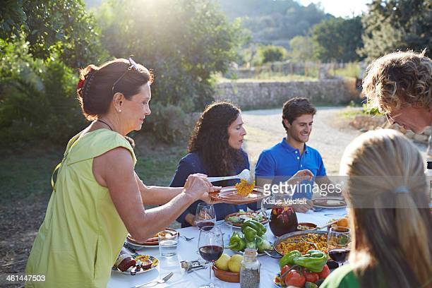 grandmother pouring paella on plate - paella stock photos and pictures