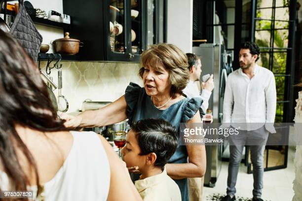 grandmother preparing food in kitchen for multigenerational family dinner party - hero and not superhero stock pictures, royalty-free photos & images