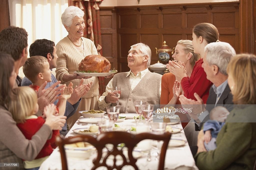 Grandmother presenting turkey to her family at the dinner table : Stock Photo
