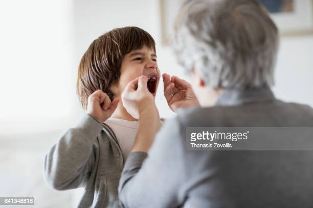 grandmother pull the milk tooth from her son with a string - personas sin dientes fotografías e imágenes de stock