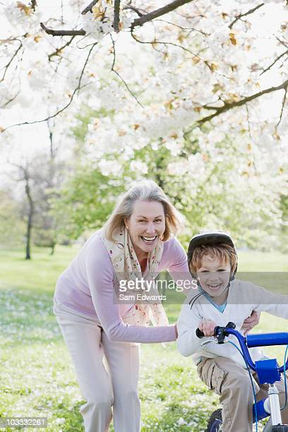 Grandmother pushing grandson on bicycle in park