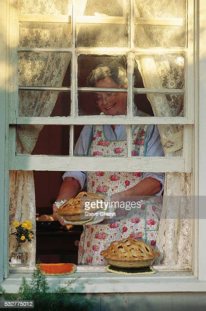 Grandmother Putting Apple Pies on Window Sill