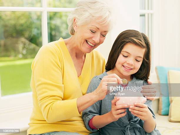 grandmother putting coin into granddaughters piggy bank - british granny stock photos and pictures