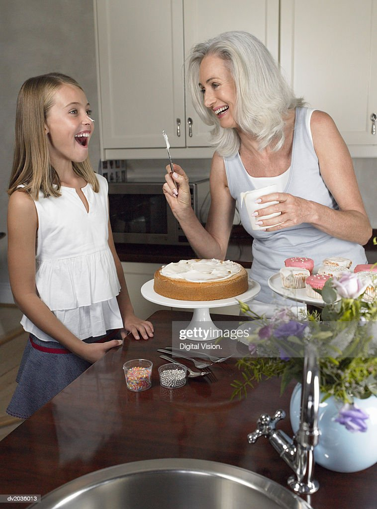 Grandmother Putting Icing on Her Granddaughter's Nose : Stock Photo