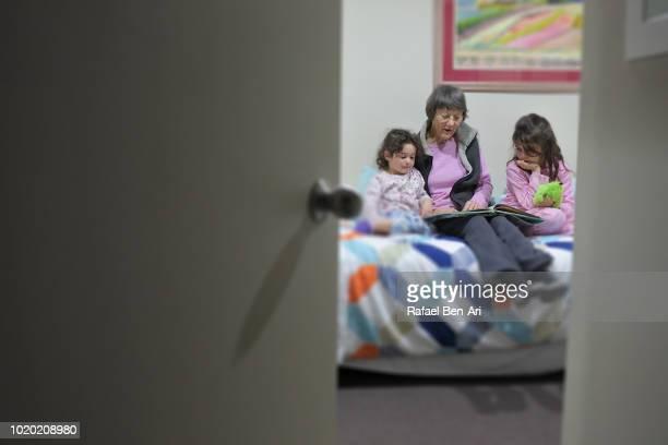 grandmother reading a bed time story to her granddaughters - rafael ben ari stock-fotos und bilder