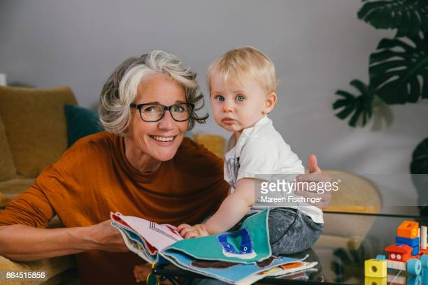 Grandmother reading a fabric book to her baby grandchild