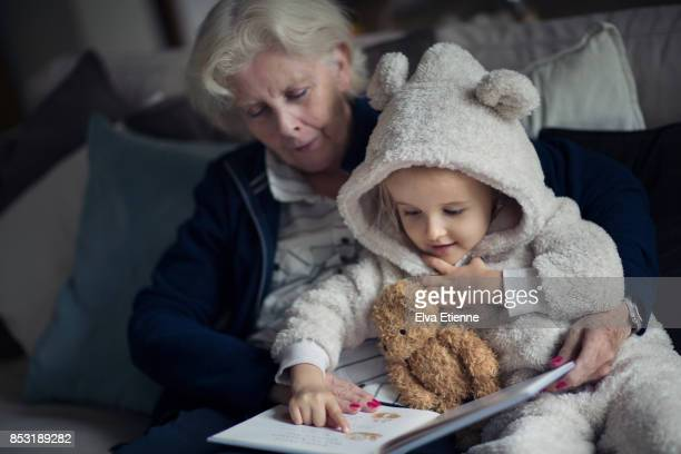 Grandmother reading a story to a child wearig cozy bear onesie.