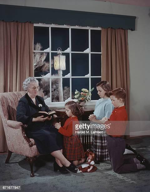 'Grandmother Reading Bible For Grand Children, Praying '