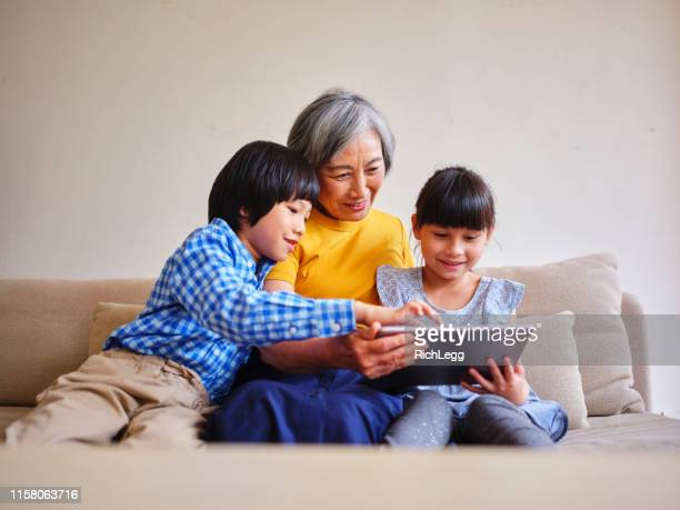 grandmother reading to children in a home in taiwan - east asian culture stock pictures, royalty-free photos & images