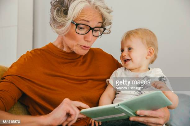 grandmother reading to her baby grandchild - thick rimmed spectacles stock photos and pictures