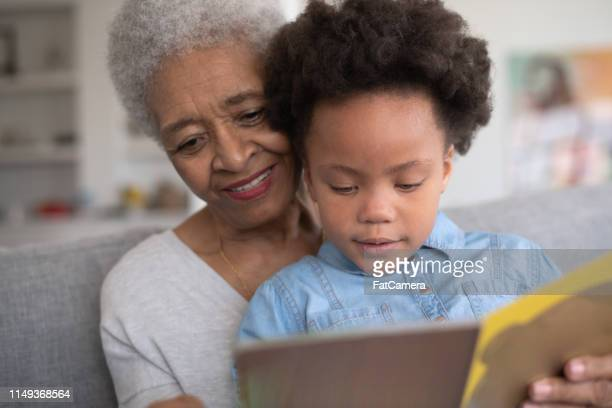 grandmother reading to her granddaughter - great grandmother stock pictures, royalty-free photos & images
