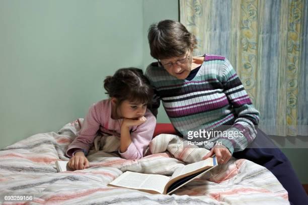 grandmother reads a book to a granddaughter in bed - rafael ben ari fotografías e imágenes de stock
