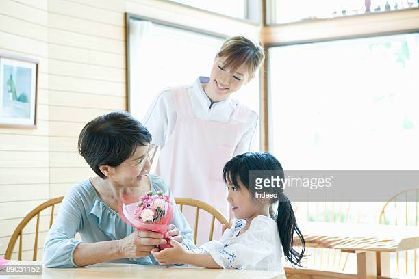 grandmother receiving flowers from granddaughter - 訪問 ストックフォトと画像