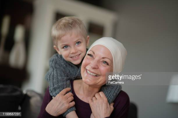 a grandmother recovering from cancer snuggles with her grandson on the couch. - bald woman stock photos and pictures