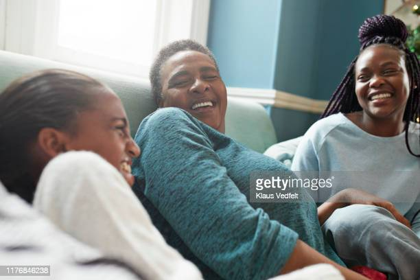 grandmother relaxing with granddaughters on sofa - sibling stock pictures, royalty-free photos & images