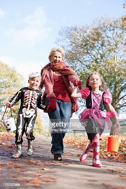 Grand-mère de course avec petits-enfants en costumes d'Halloween
