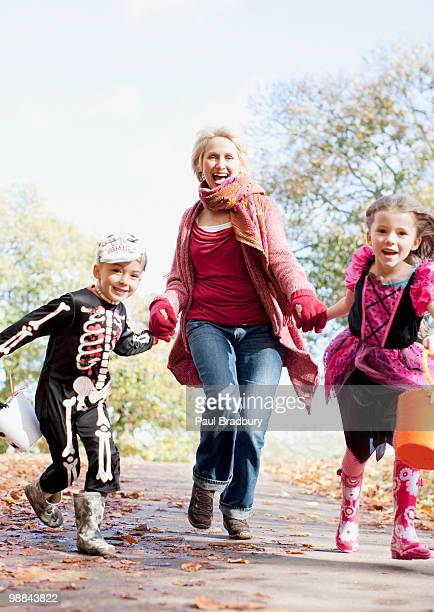 Grandmother running with grandchildren in Halloween costumes