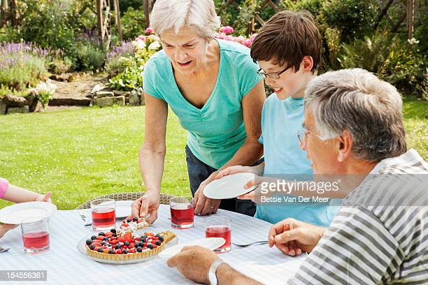 grandmother serving cake to family in garden.