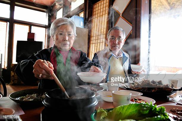 grandmother serving soup - koreanischer abstammung stock-fotos und bilder