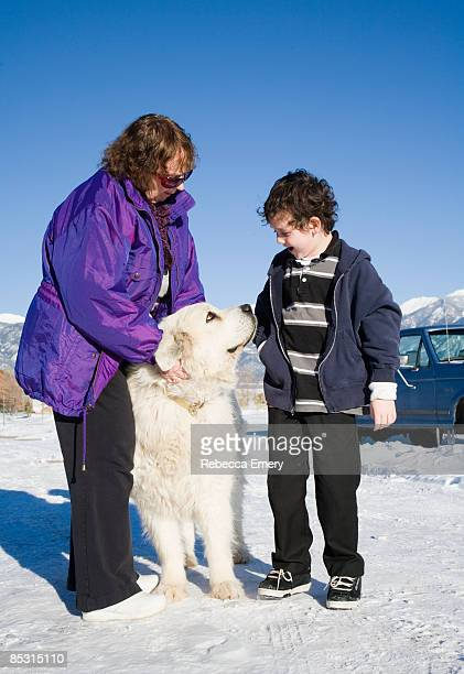 grandmother showing dog to grandson - emery stock photos and pictures