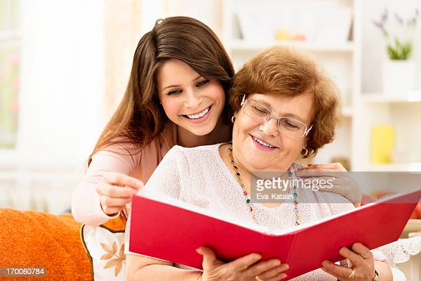 Grandmother showing old photos to her granddaughter