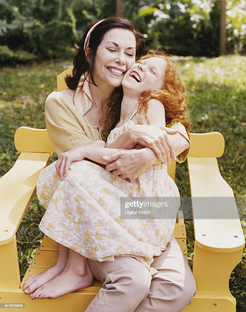 Grandmother Sits on a Wooden Chair Giving Her Granddaughter a Cuddle : Stock Photo
