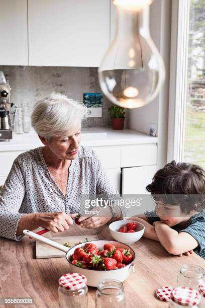 grandmother sitting at kitchen table, preparing strawberries, grandson sitting beside her, watching - western europe stock pictures, royalty-free photos & images