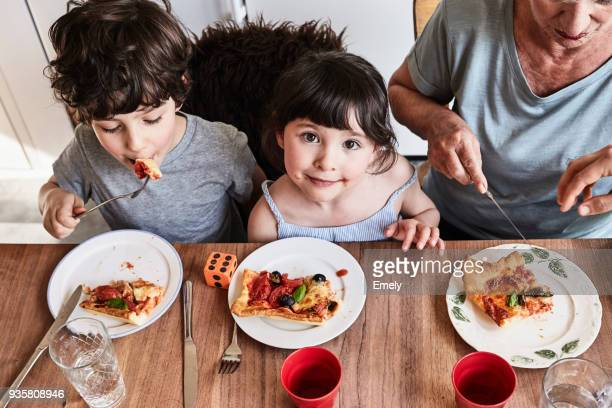 grandmother sitting at kitchen table with grandchildren, eating pizza, elevated view - comfort food stock pictures, royalty-free photos & images