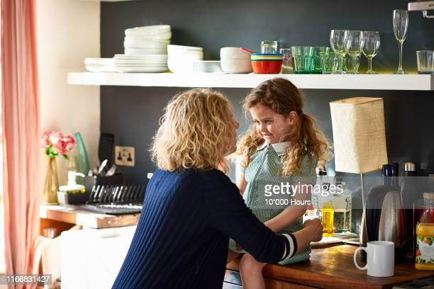 grandmother speaking closely to young granddaughter in kitchen - showing respect stock pictures, royalty-free photos & images