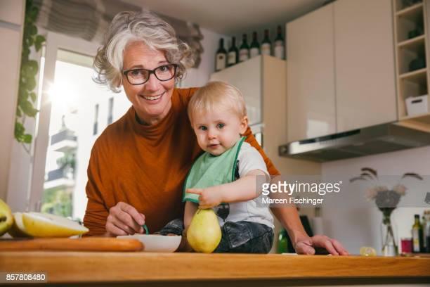 Grandmother spoon-feeding pear puree to her baby grandchild