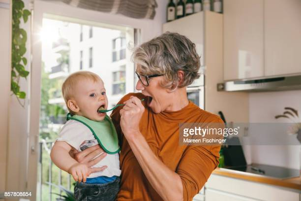 Grandmother spoon-feeding pear puree to her baby grandchild