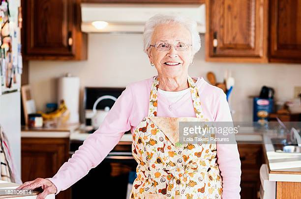 grandmother standing in her kitchen - schürze stock-fotos und bilder