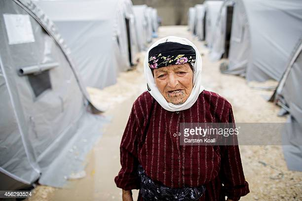 A grandmother stands between tents in a refugee camp after crossing from Syria into Turkey in Suruc September 28 2014 south of Sanliurfa Turkey...
