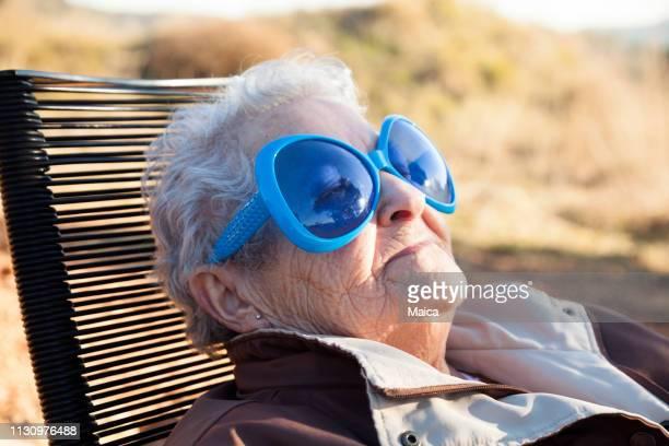 grand-mère bronzette avec de jolis verres - bronzage humour photos et images de collection